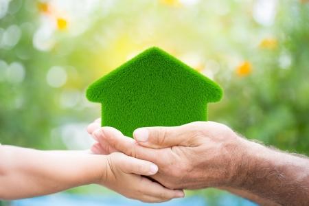 Familia hierba holding casa en manos contra el resorte verde concepto de protección de fondo para el Medio Ambiente Foto de archivo