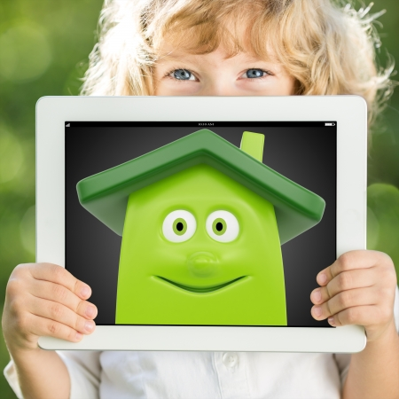 Happy child holding tablet PC with green house on screen  Renovation concept Stock Photo