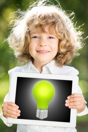 lightbulbs: Child holding tablet PC with green light bulb on screen against blurred spring background  Creativity technology concept Stock Photo