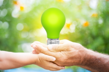 solar energy: Senior man and baby holding green light bulb in hands against blurred spring background