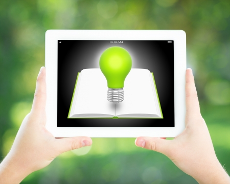 Student holding tablet PC with ebook and light bulb in hands against spring green background  Education technology concept photo