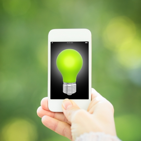 Smart phone with light bulb in hand against green spring background  Ecology concept photo