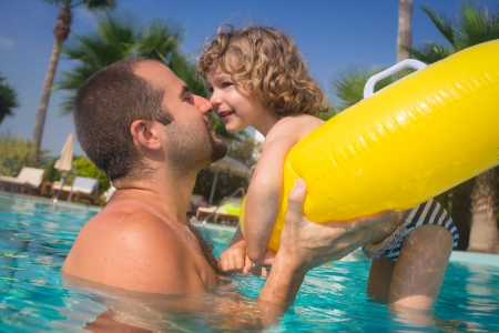 Happy kid with father playing in swimming pool. Summer vacations concept