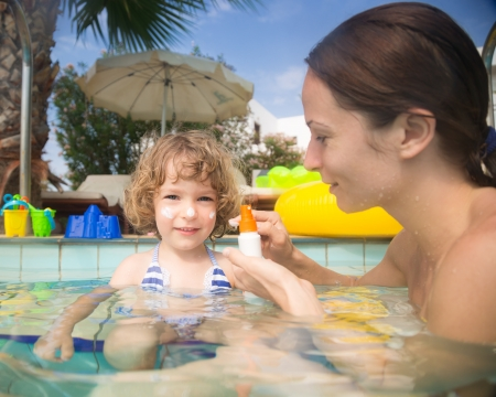 Mother applying sunblock lotion on child in swimming pool. Summer vacations concept photo