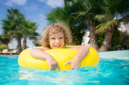 Happy child playing in swimming pool. Summer vacations concept photo