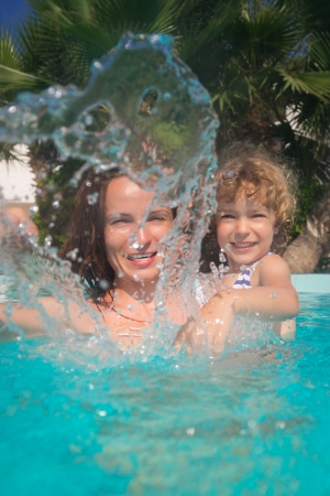 Happy family playing in swimming pool. Summer vacations concept photo