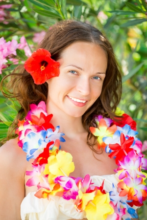 Happy smiling woman with flower lei garland of orchids. Summer vacations concept photo