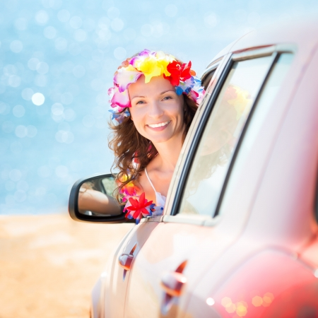 Happy woman driver wearing hawaiian flowers garland on the beach. Summer vacations concept photo