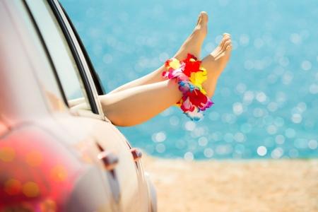 Vrouw benen tegen smaragdgroene zee en strand achtergrond. Zomervakanties begrip