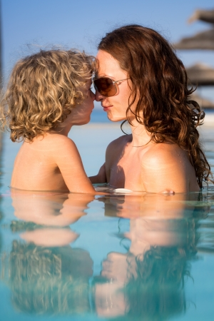 Smiling woman with child relaxing in swimming pool. Summer vacations concept photo