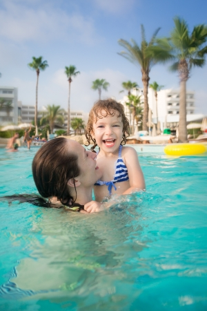Happy family playing in swimming pool  Summer vacations concept photo