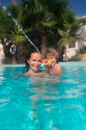 Happy child and mother playing in swimming pool  Summer vacations concept photo