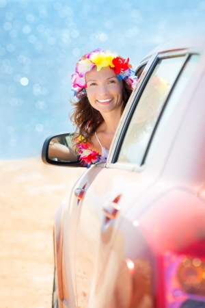 Happy woman driver wearing hawaiian flowers garland on the beach  Summer vacations concept photo