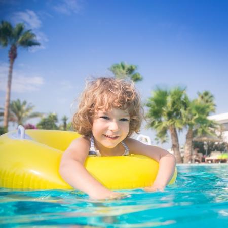 enfant qui joue: Enfant heureux jouant dans la piscine d'�t� concept de vacances Banque d'images