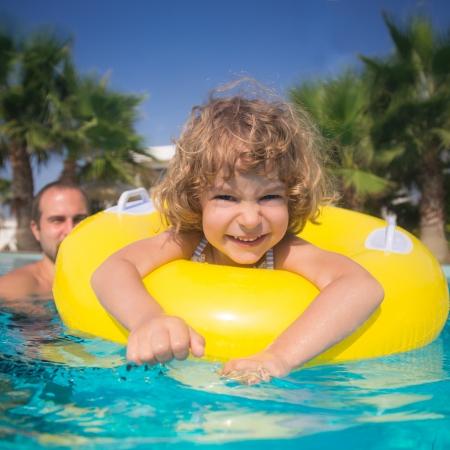 スイミング プールの夏の休暇の概念で遊んでの父親と一緒に幸せな子供