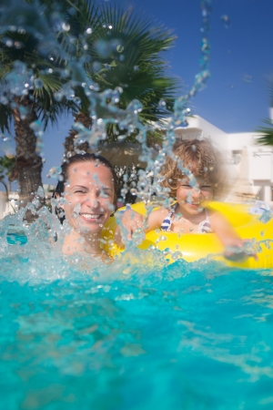 Happy family playing in swimming pool  Summer vacations concept