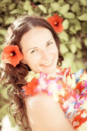 Happy smiling woman with flower lei garland of orchids  Summer vacations concept photo
