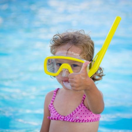 Niño feliz que muestra el pulgar hacia arriba signo contra el fondo de la piscina de natación