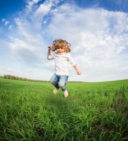 boy jumping: Ni�o feliz saltando en el campo verde contra el cielo azul concepto de vacaciones de verano Foto de archivo