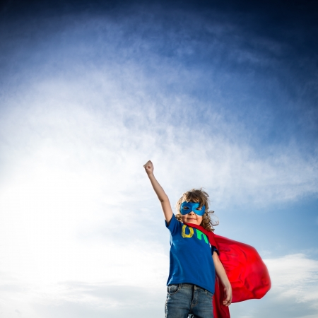 child sport: Superhero kid against dramatic blue sky background Stock Photo