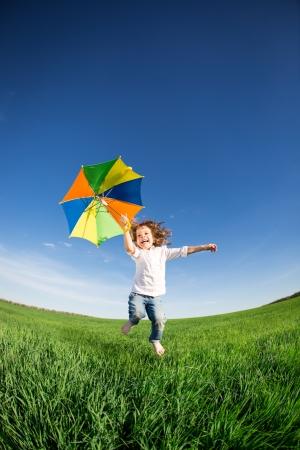 niños bailando: Niño feliz saltando en el campo verde contra el cielo azul concepto de vacaciones de verano Foto de archivo