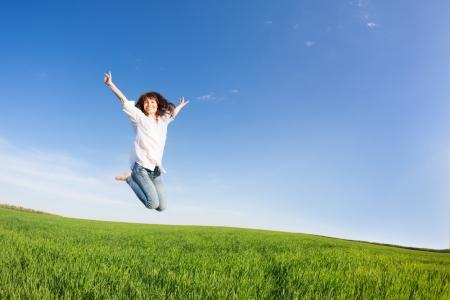 Donna felice che salta nel campo verde contro il cielo blu concetto di vacanza estiva