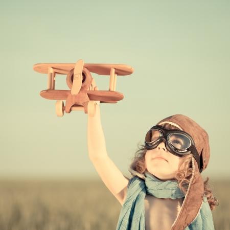 vendimia: Niño feliz jugando con avión de juguete contra el fondo del cielo azul del verano