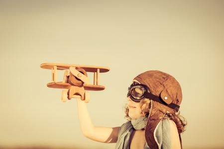 행복한 아이는 파란 여름 하늘 배경에 장난감 비행기와 재생
