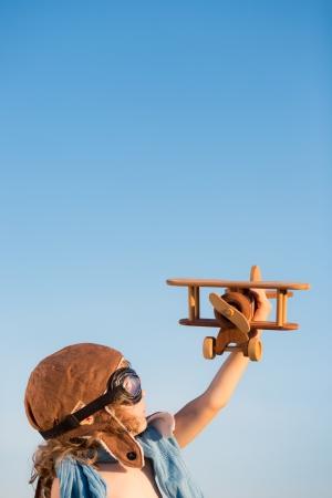 Felice bambino giocando con aeroplano giocattolo su sfondo blu del cielo estivo Archivio Fotografico