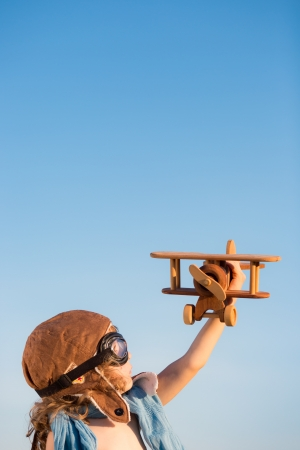 aviator: Happy kid playing with toy airplane against blue summer sky background
