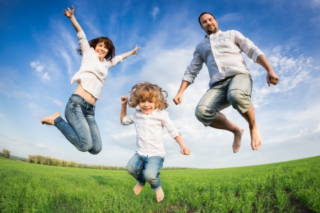 Happy active family jumping in green field against blue sky. Summer vacation concept Stock Photo