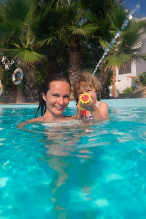 Mother and child playing in swimming pool photo