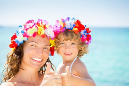 hawaiian lei: Happy family showing thumb up sign against blue sea background