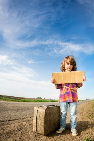 Lonely girl with suitcase standing about road and holding paper with copy space in hands photo