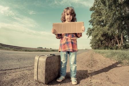 ni�os tristes: Muchacha sola con la maleta que se coloca sobre el camino y la celebraci�n de papel con copia espacio en las manos