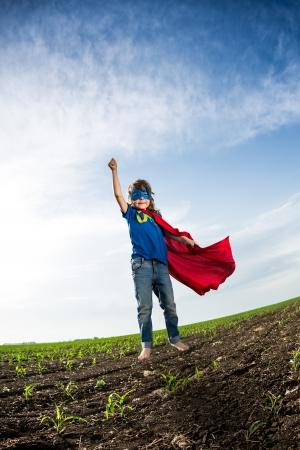kids costume: Superhero kid jumping against dramatic blue sky background Stock Photo