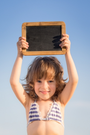 Happy child holding blank blackboard against blue sky background photo
