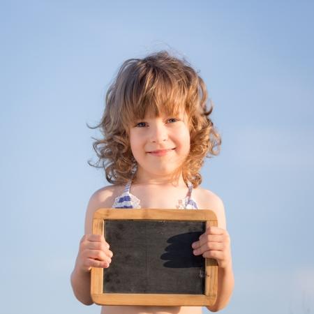 Happy child holding blank blackboard against blue sky background photo