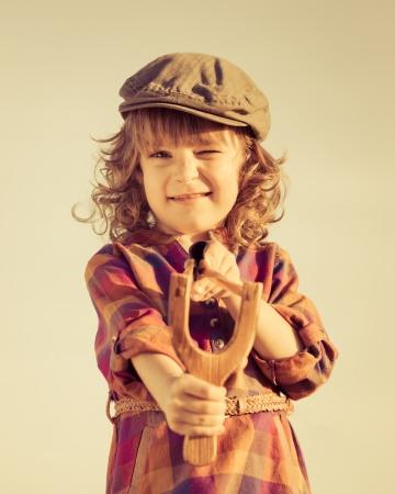 toned image: Funny kid shooting wooden slingshot. Retro toned image