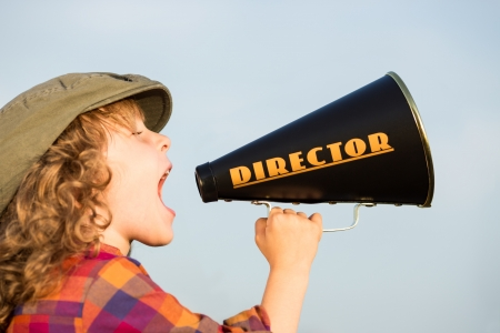 Kid shouting through director vintage megaphone Stock Photo