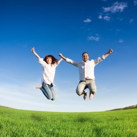행복한 커플은 푸른 하늘 여름 휴가 개념에 대해 그린 필드에서 점프 스톡 콘텐츠