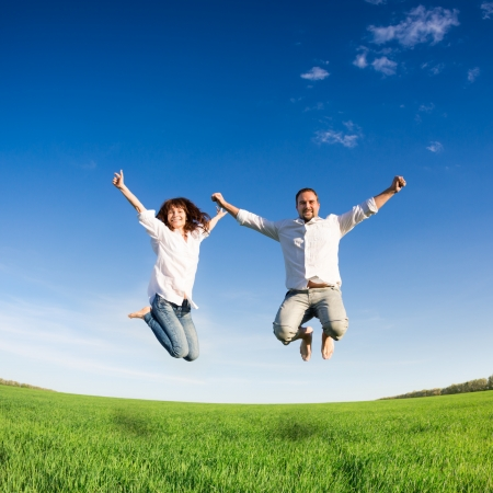 parejas felices: Pareja feliz saltando en el campo verde contra el cielo azul concepto de vacaciones de verano Foto de archivo