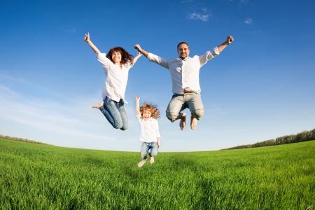 Lycklig familj hoppar i grönt fält mot blå himmel Sommarlovet koncept Stockfoto