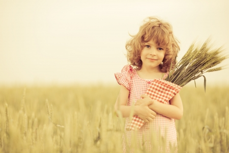 Happy child in autumn wheat field photo