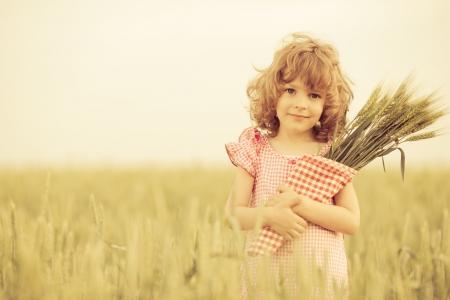 cultivo de trigo: Ni�o feliz en el campo de trigo de oto�o