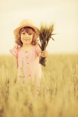 baby corn: Happy child in autumn wheat field