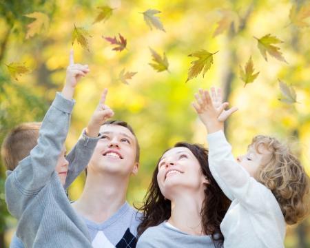 hombre cayendo: Familia feliz que se divierte al aire libre en el parque de oto?o contra fondo borroso hojas