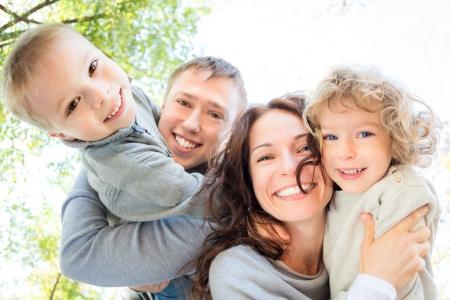 stile di vita: Basso angolo di vista di famiglia felice in autunno parco