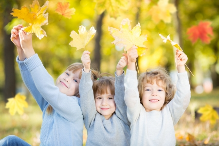 children playing outside: Happy children with maple leaves in autumn park