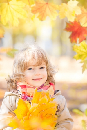Happy child with maple leaves in autumn park photo